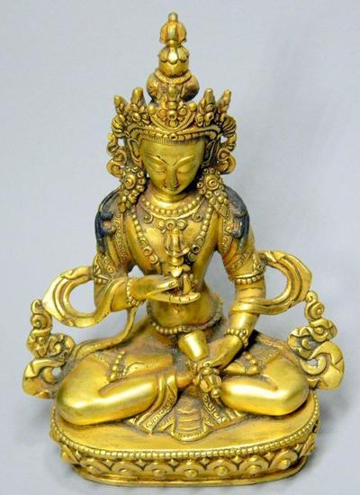 Tibetan Gilt Bronze Figure of Buddha Akshobhya Holding an Oil Lamp