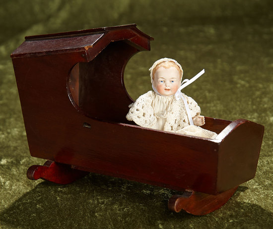 "5"" German all-bisque baby with wooden hooded cradle. $300/400"