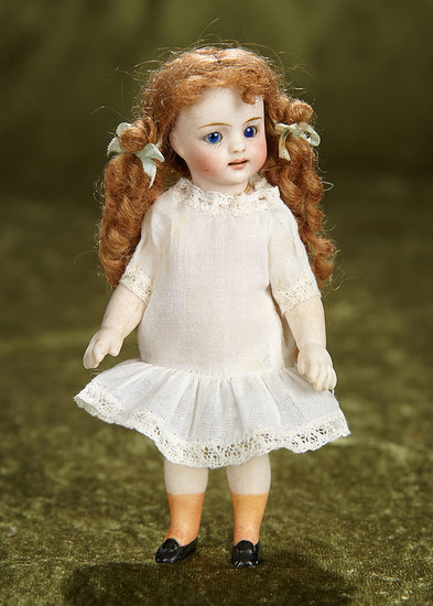 "5"" German all-bisque doll with distinctive beautiful face, unusual orange socks. $600/800"