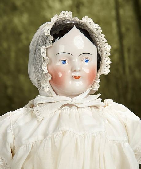"26"" German porcelain doll with pink-tinted complexion and nice antique costume. $400/500"