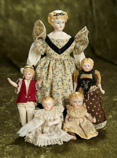 Family of miniature German bisque dolls with sculpted hair and antique costumes. $800/1200