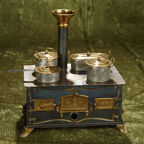 """10""""l. German tinplate toy stove with brass doors and original pots and pans. $400/600"""