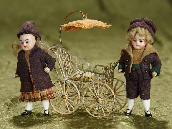 """Pair, 3 1/2"""" German all-bisque dolls in original school costumes, with carriage. $400/500"""