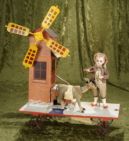 """19""""h. (15""""l.)  French mechanical pull-toy """"Boy at the Windmill with Unruly Donkey"""". $1200/1500"""