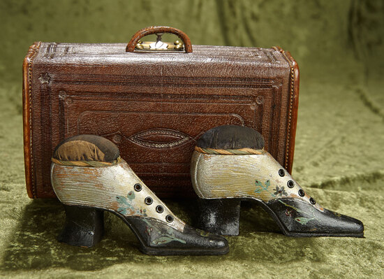 "9""l. Leather bound case with fitted interior, and carved wooden shoes as pincushions. $400/500"