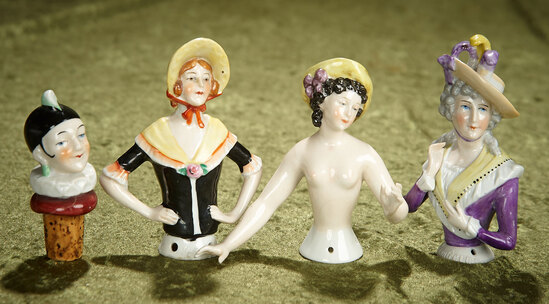 """4"""" Three German porcelain half-dolls and cork bottle head, with sculpted decorations. $300/400"""