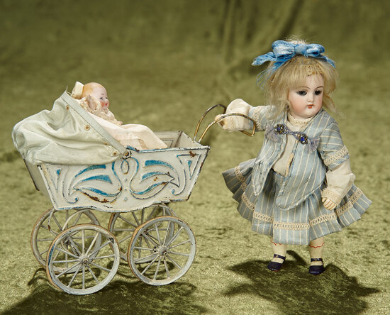 "6"" German bisque miniature doll with pressed tin carriage and baby. $400/500"