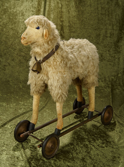 "18""l. German mohair toy lamb on wheeled base with blue glass eyes. $600/800"