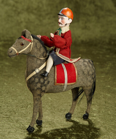 "12"" German bisque doll as jockey with sculpted cap and moustache, seated on covered horse. $800/1200"