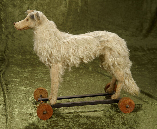 """14"""" White mohair dog pull toy with glass eyes on cast iron base with wooden wheels."""