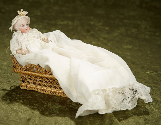 "5"" German all-bisque character baby, antique gown, in woven bassinette. $400/500"