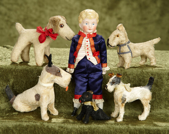 "2""-7.5""  Small German bisque boy with his grouping of small paper mache dogs."