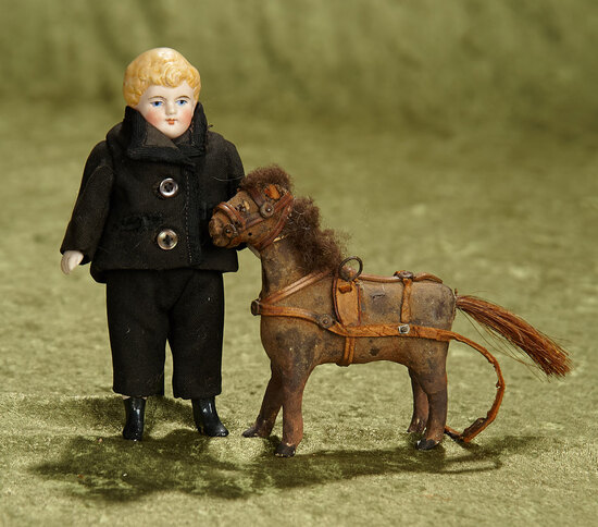 """5 1/2"""" German all-bisque boy with sculpted hair, antique costume, toy horse. $300/400"""