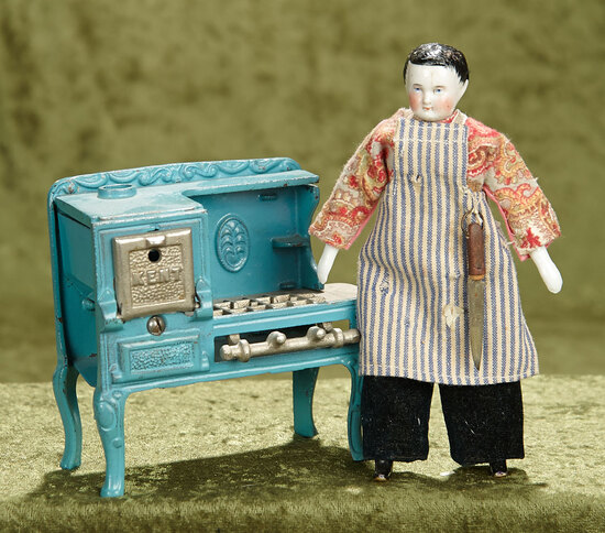 """4 1/2""""h. American cast iron gas stove by Kent, and German porcelain doll as chef. $400/500"""