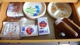 Assorted paper plates, napkins, plastic flatware, wicker plate holders, wooden napkin holder.