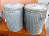 Pair of old time galvanized garbage cans. Usable with some cracks.
