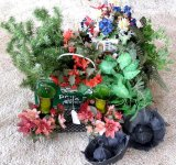 Quantity of faux flowers, ferns, evergreen, etc. Also wrought iron candle holder, more.