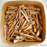 Box 3/4 full of heavy duty old wooden clothespins. Box measures 9-1/2