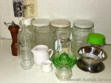 Glass canisters, heavy glass milk pitcher, creamer, pepper grinder, green Depression glass reamer,