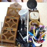 Office supplies including letter sorter, cup of pens and pencils, alarm clock, lamp, cordless