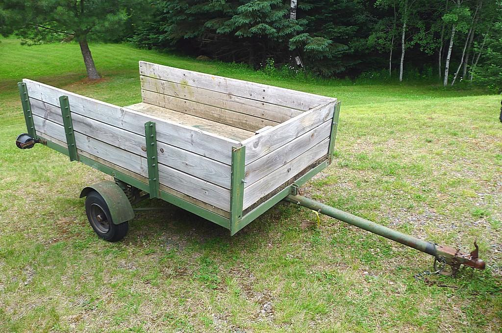 """Two wheel metal framed trailer with wood sides and bottom. Approx. 7' x 4' x 17"""" high. Tire size is"""