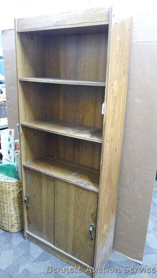Storage cabinet with 3 shelves in upper section and 2 shelves behind sliding doors on bottom.