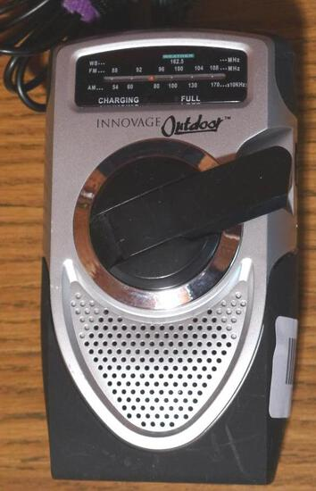 """Innovage Outdoor hand crank weather band AM/FM radio is 3-1/2"""" x 6"""". Comes with power cord and ear"""