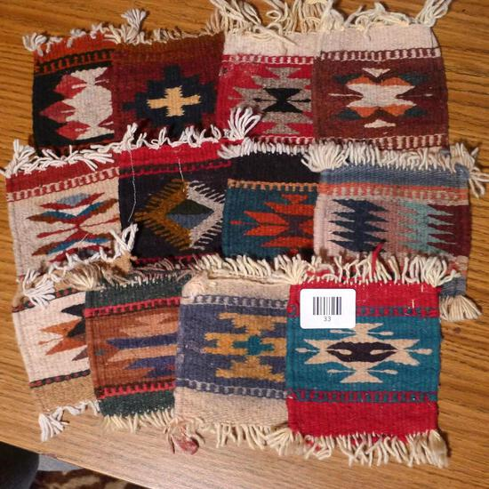 """Twelve woven 5"""" x 6"""" mini rugs that would make great coasters or wall decorations."""