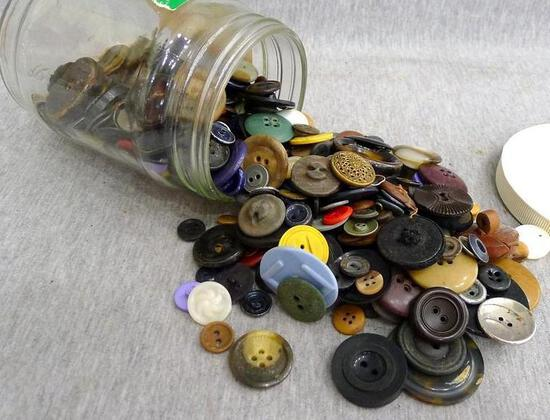 """Metal and other buttons in a 5-1/2"""" jar. Metal one is 1-1/2"""" wide."""