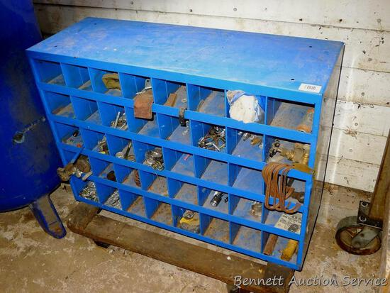 """Metal storage cabinet has 40 compartments and is 12"""" x 34"""" x 24"""" tall. Comes with contents and is on"""