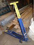 Heavy duty floor hydraulic floor jack is approx. 4' long. Raises and lowers.