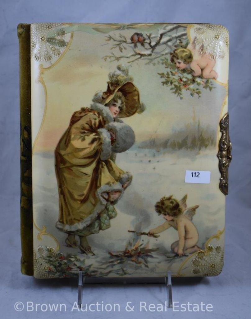 Vintage photo album with celluloid cover featuring winter scene/woman and cherubs, artist signed