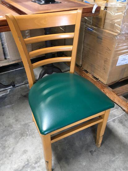 Dining chairs with green padded seats