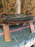 Vintage camel saddle. Wood frame with flower designs and leather seat. Approx. 17