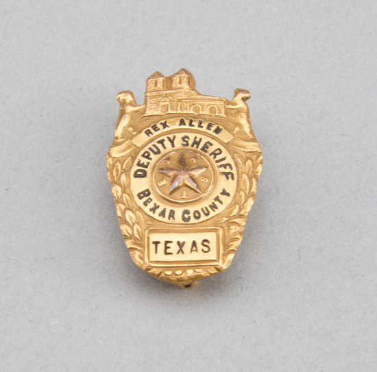 "Gold Shield Badge, marked Rex Allen, Deputy Sheriff Bexar County, 1 1/4"" tall.  Badge will be accomp"