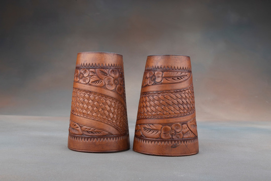 A pair of vintage leather Roping Cuffs, floral tooled with basket weave center.  Cuffs have inside l