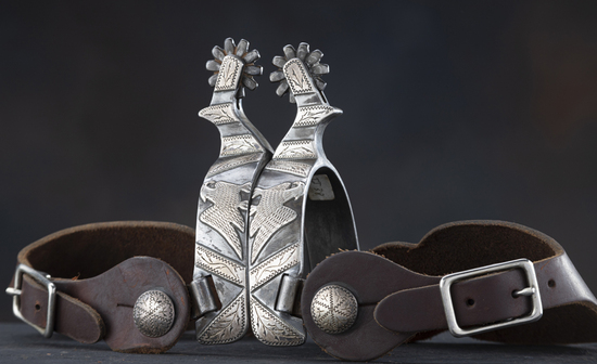 A pair of single mounted, hand engraved silver overlay Spurs by noted Texas Bit and Spur Maker Ray A