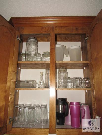Contents of kitchen cabinet includes glass tumblers mugs canisters and pitchers