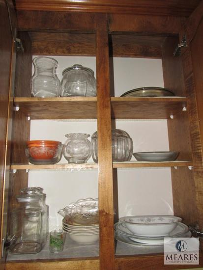 Contents of kitchen cabinet includes glass bowls canister bowls and plates