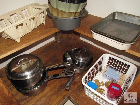 Contents of kitchen cabinet includes pots pans and cake pans