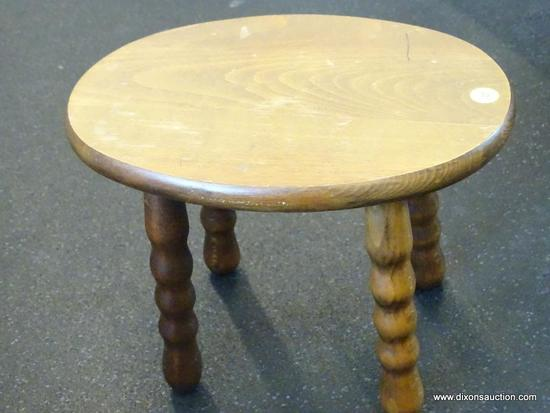 (WIN) OVAL WOODEN FOOTSTOOL WITH SPOOLED LEGS; MEASURES 12.5 IN X 9.5 IN X 9.5 IN TALL. HAS PRINTED