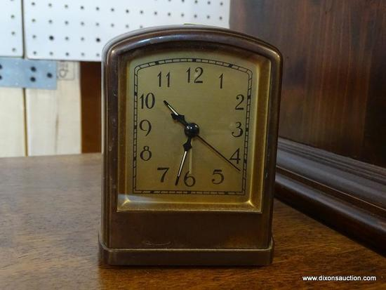 (R1) POTTERY BARN ALARM CLOCK; BROWN METAL CASE WITH BRASS COLORED FACE AMD A SLIGHTLY ROUNDED TOP.