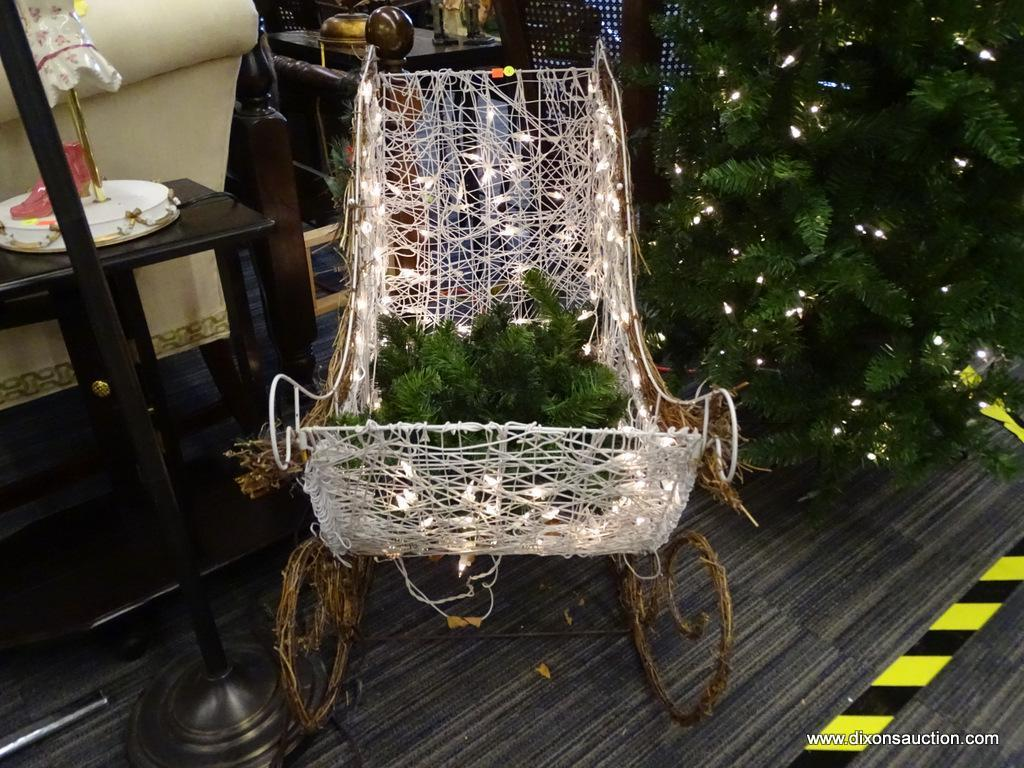 PRE-LIT SLEIGH; WHITE WICKER AND BROWN VINE WOVEN SLEIGH WITH WHITE CHRISTMAS LIGHTS. HAS A RED BOW