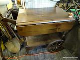 TEA CART; PINE TEA CART WITH DROP-SIDES AND A LOWER SHELF. HAS A TURNED HANDLE AND SPINDLE WHEEL