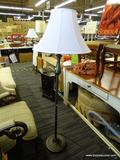 FLOOR LAMP; WHITE BELL SHAPED LAMPSHADE ATOP A POST WHICH IS DARK BRUSHED GREY METALLIC COLOR, WITH