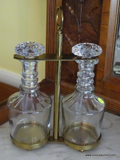 (DR) PAIR OF MATCHING CUT GLASS DECANTERS WITH STOPPERS IN BRASS HOLDER WITH LOOP HANDLE; EACH