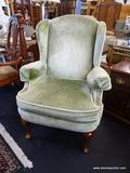 GREEN UPHOLSTERED WING CHAIR; HAS CREAM COLORED TRIM AND MAHOGANY BONES WITH QUEEN ANNE LEGS AND