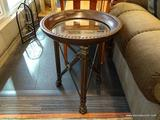 ROUND METAL END TABLE; HAS A GLASS INSERT AND PAW STYLE FEET. HAS A BRONZE TONED RIM WITH BRASS