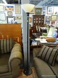 TORCHIERE LAMP; BLACK IN COLOR WITH AN OFF-WHITE SHADE. MEASURES 69 IN TALL