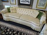 2 CUSHION SOFA; MADE BY WATERS FURNITURE CO. IS CREAM IN COLOR WITH GREEN TRIM AND FLORAL PATTERN